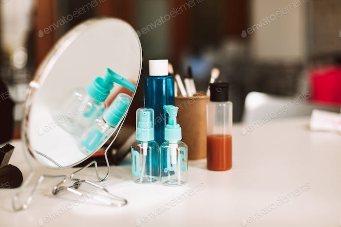 Close up little mirror and cosmetic products on table