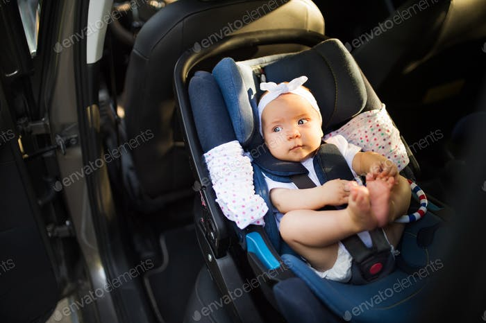 Little baby fastened with security belt in safety car seat.