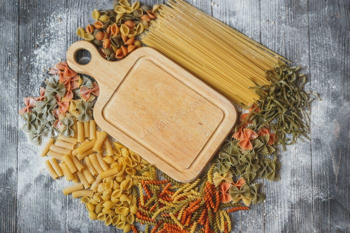 Cutting wooden board in the center with space for your text lies in the abundance of pasta