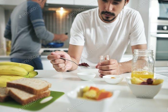 Gay People Having Breakfast Cooking In Home Kitchen