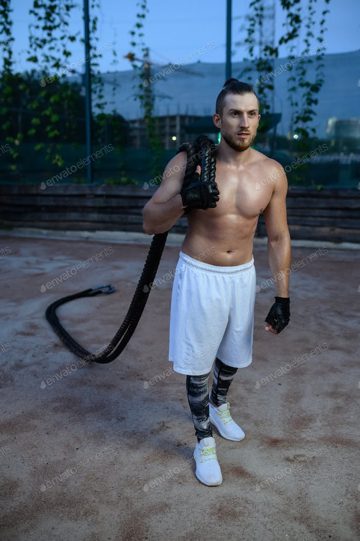 Man poses with crossfit ropes, street workout