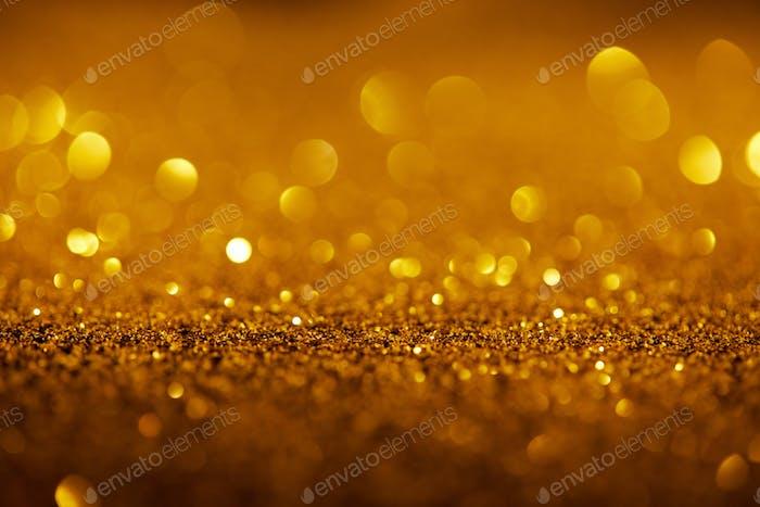 abstrakter Hintergrund mit Goldglitter und Bokeh