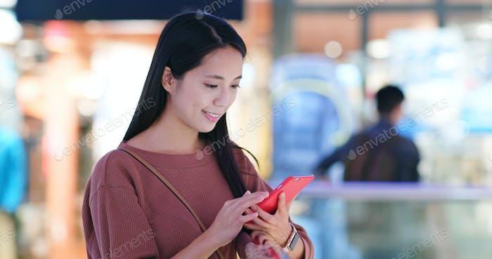 Frau überprüfen Sie den Rabatt im Handy im Einkaufszentrum Plaza