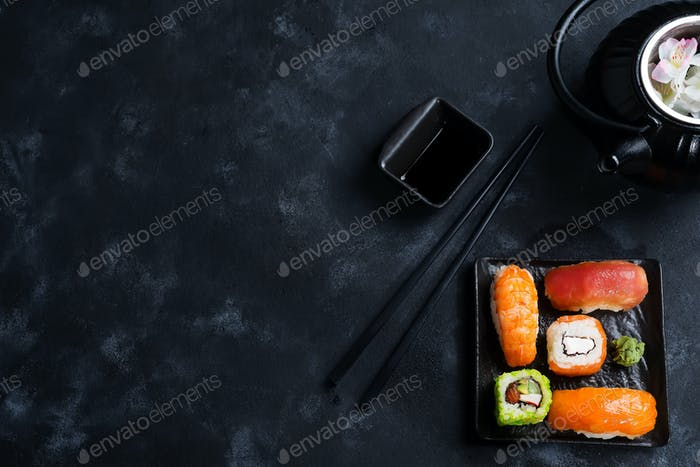 Asian food background with black iron teapot and sushi set on slate plate on black stone table, flat