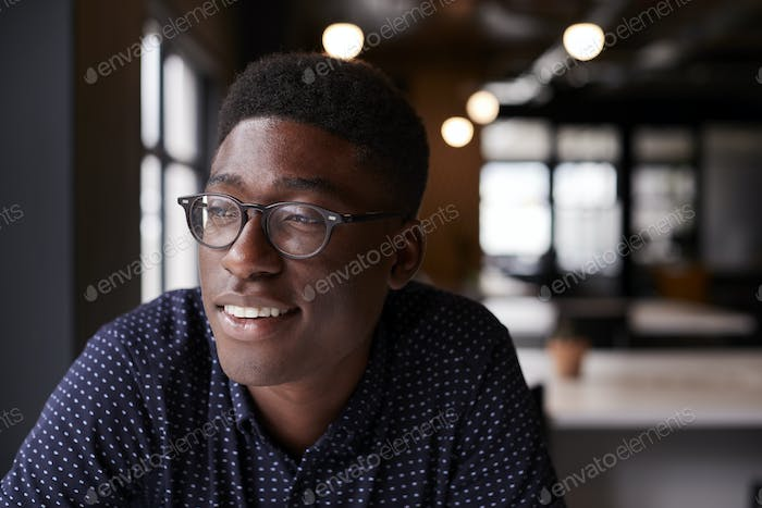 Young black male creative sitting at a desk in an office looking out of the window smiling, close up