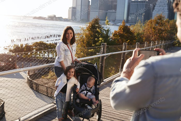 Young family with two daughters taking a photo on footbridge