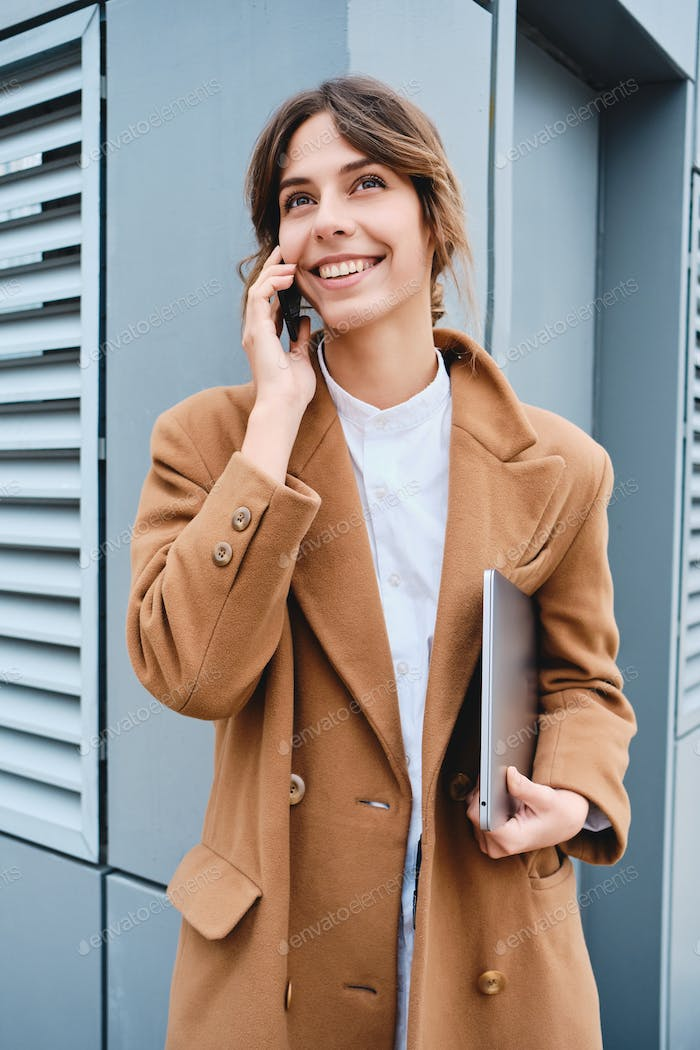 Young pretty smiling businesswoman in coat with laptop happily talking on cellphone outdoor