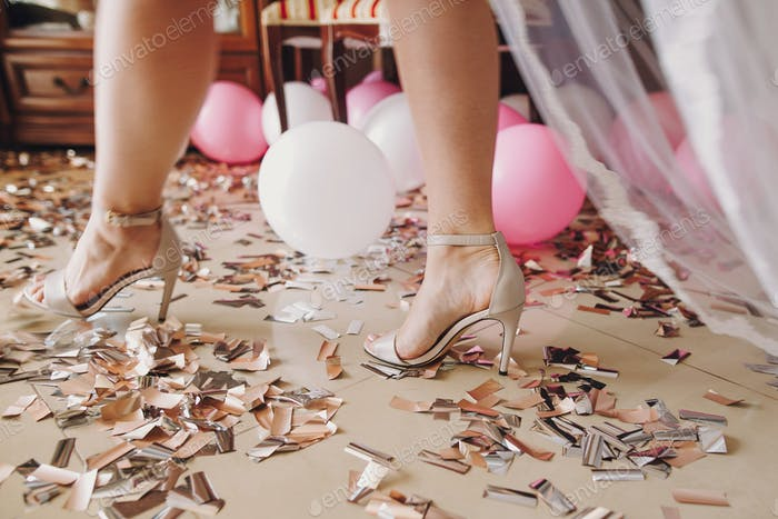 Girl legs in stylish white shoes walking on gold and silver confetti