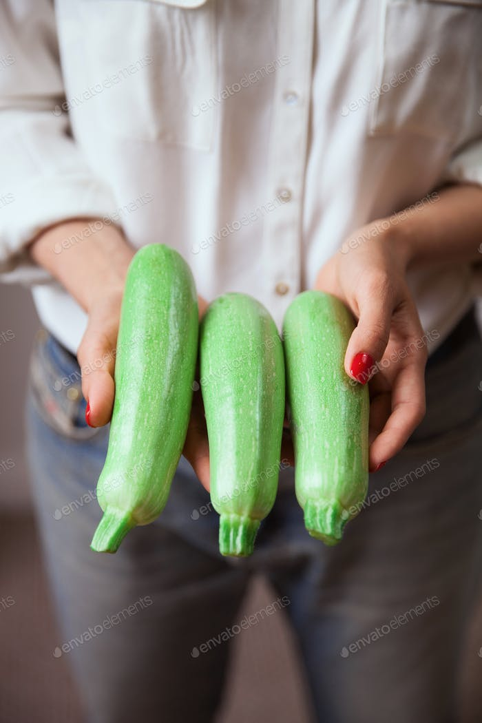 Young woman hands with zucchini