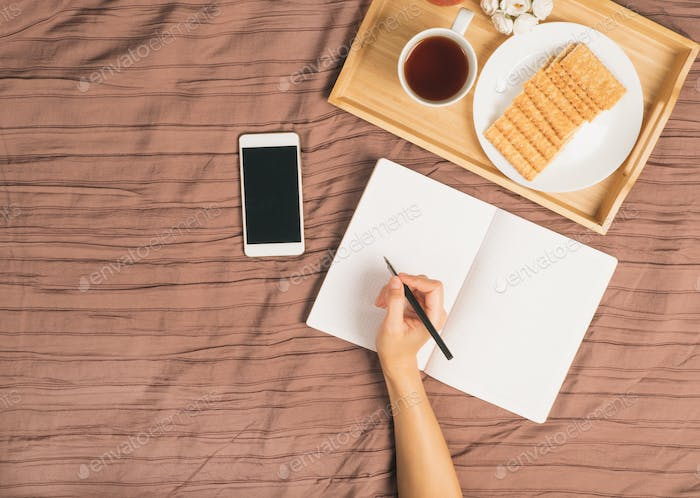 woman writes in large white open notebook, lay on bed with smartphone, breakfast tray