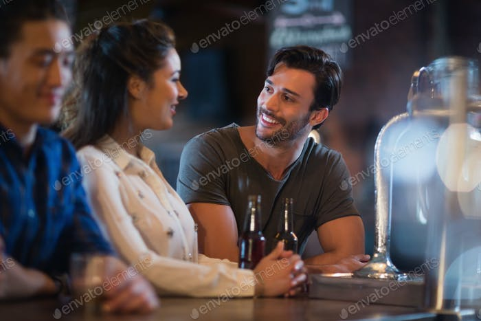 Smiling friends interacting at bar counter