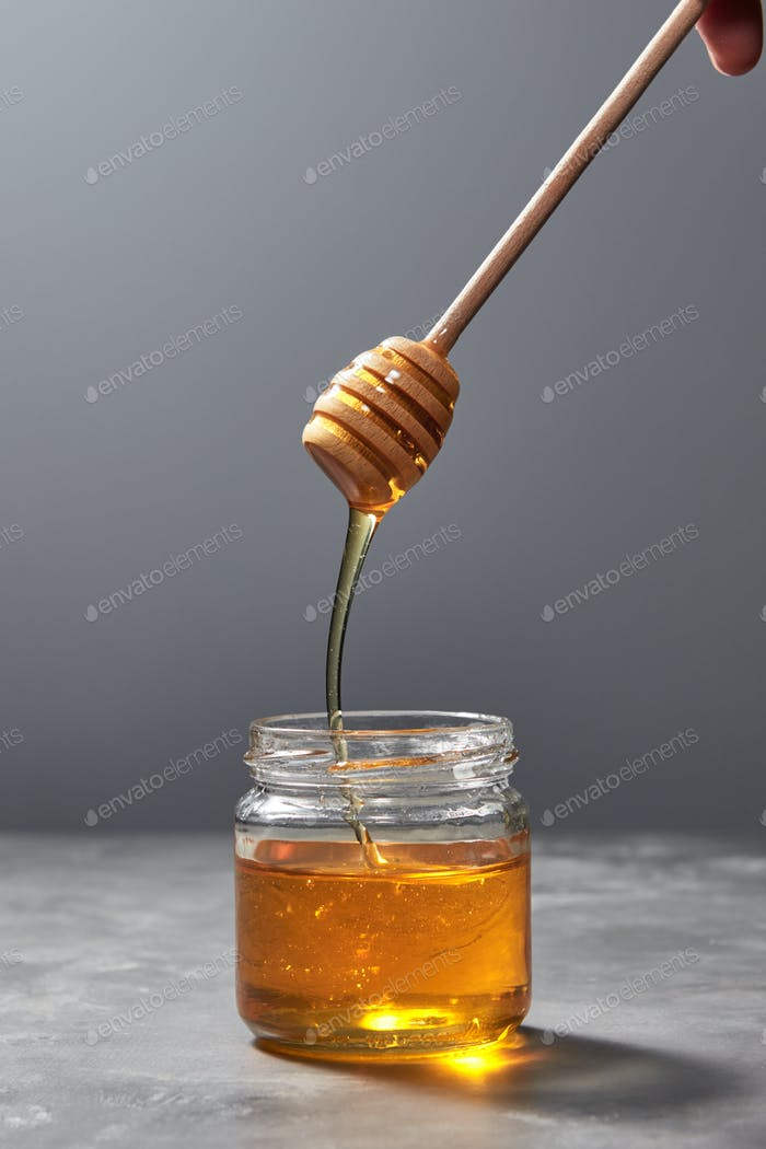 Sweet flower natural honey dripping to a glass jat with yellow transparent dessert on a gray