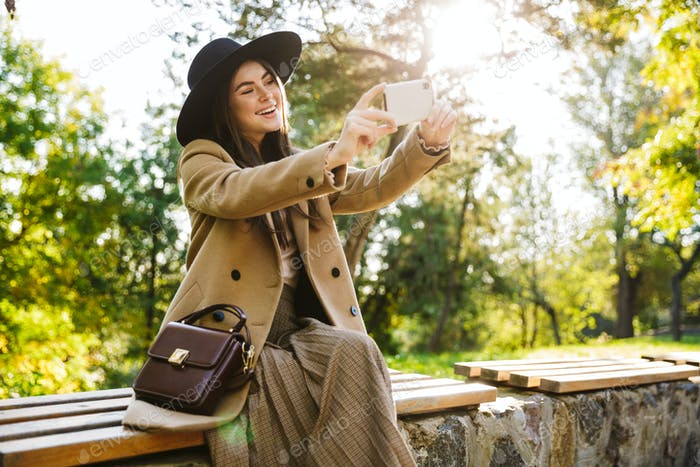 Image of fashion woman using smartphone while sitting on bench in park
