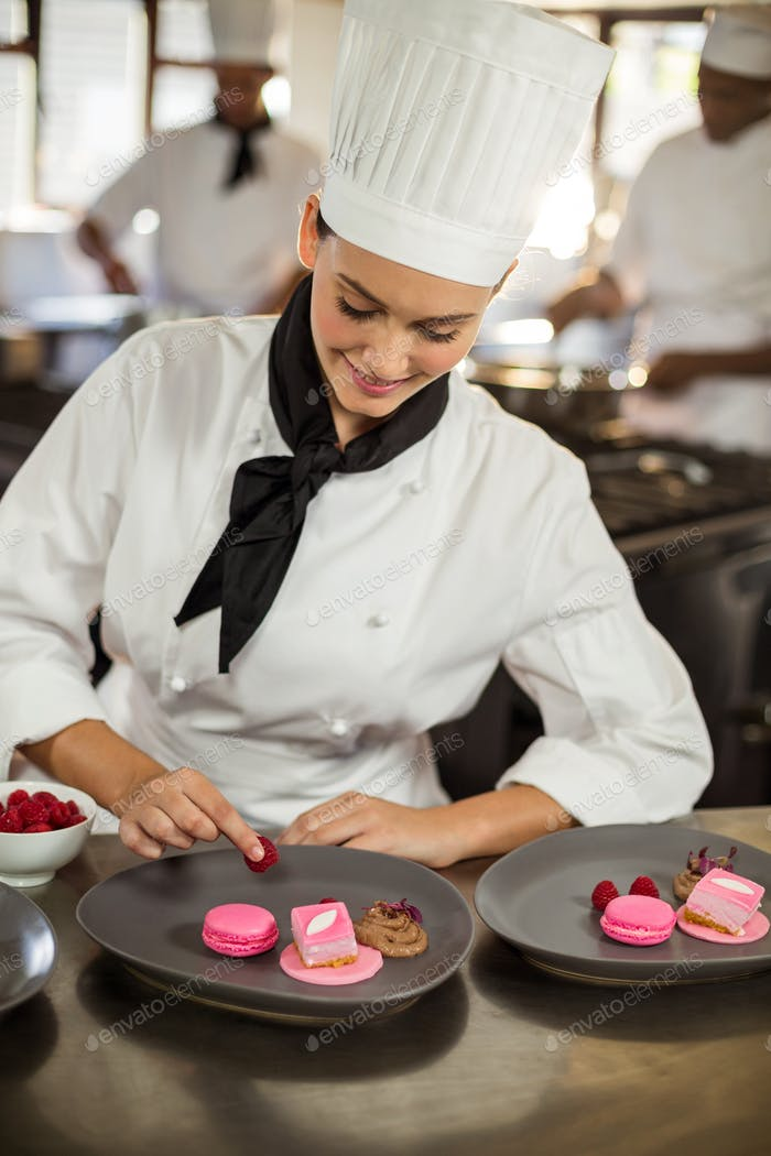 Smiling female chef finishing dessert plates