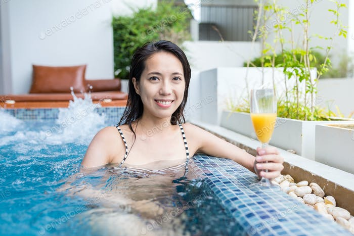 Woman enjoy her drink in jacuzzi spa