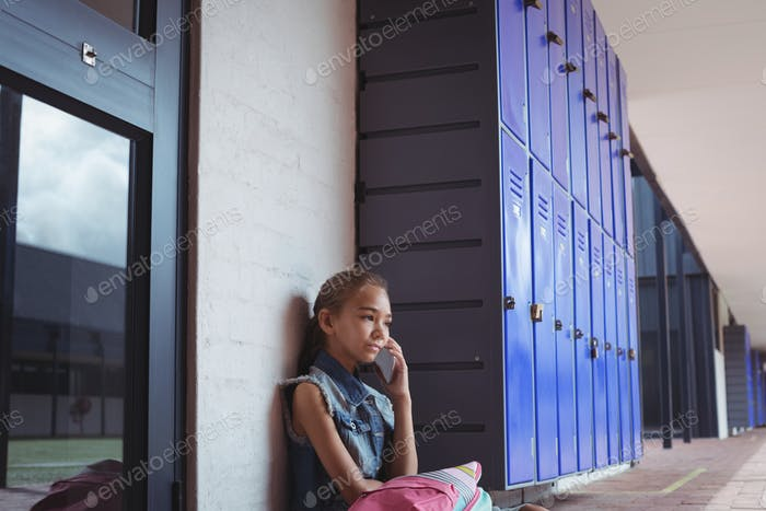 Elementary schoolgirl talking on mobile phone while sitting by lockers