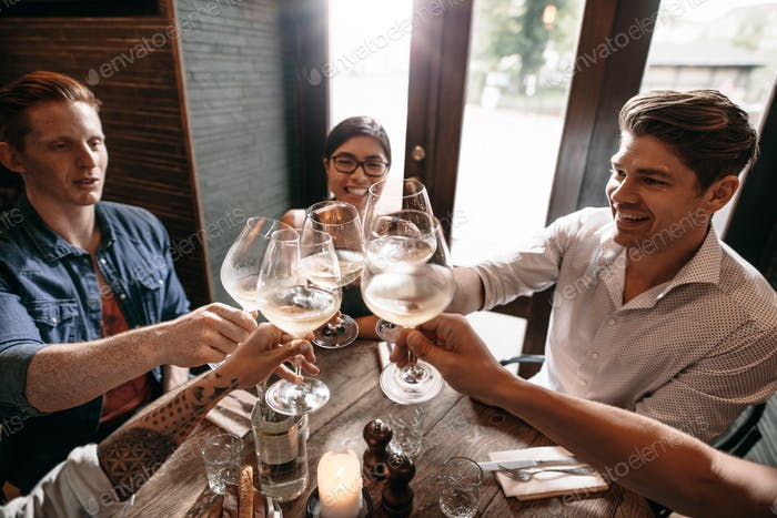 Group of people toasting wine at restaurant