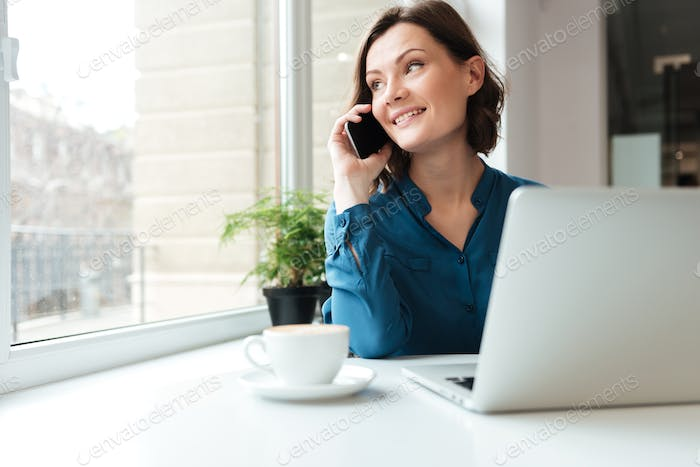 Happy smiling woman talking on mobile phone