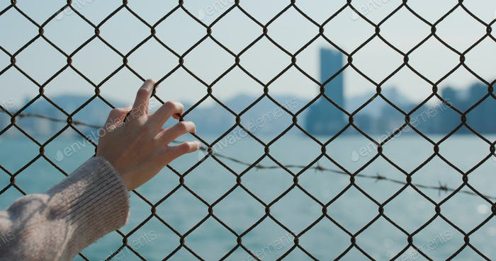 Woman hold hand on fence
