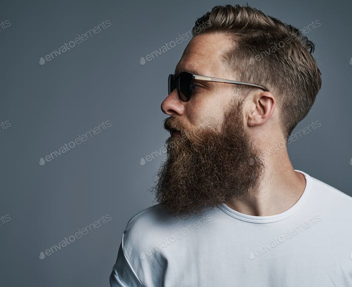 Cool young man with a beard wearing sunglasses looking sideways