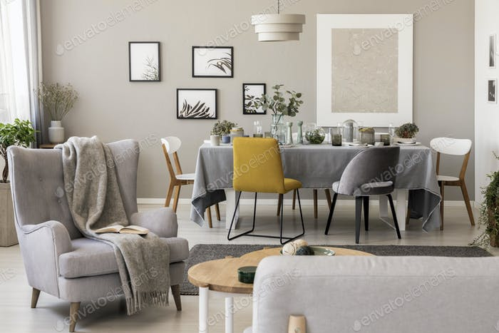 Blanket on grey armchair in spacious dining room interior with c