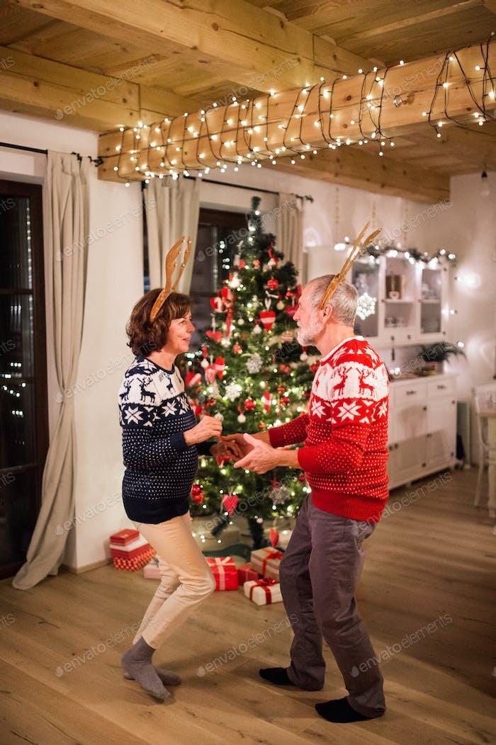 Seniorenpaar tanzen am Weihnachtsbaum am Abend.