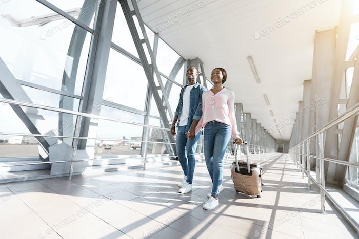 Romantisches afrikanisches Paar zu Fuß mit Koffern zum Boarding Gate am Flughafen