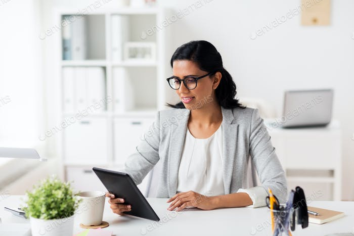 smiling businesswoman with tablet pc at office