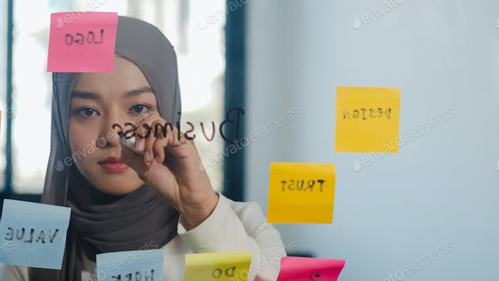 Asia muslim lady write information, strategy, reminder on glass board in new normal office.