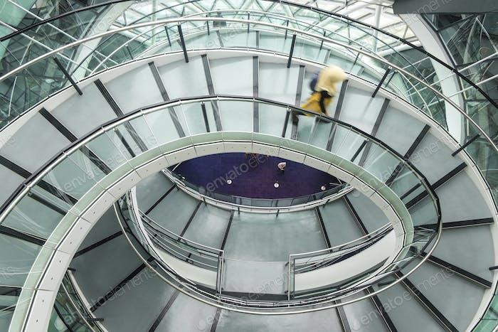 Innenansicht des Gebäudes mit Person zu Fuß entlang Glas und Metall Wendeltreppe.