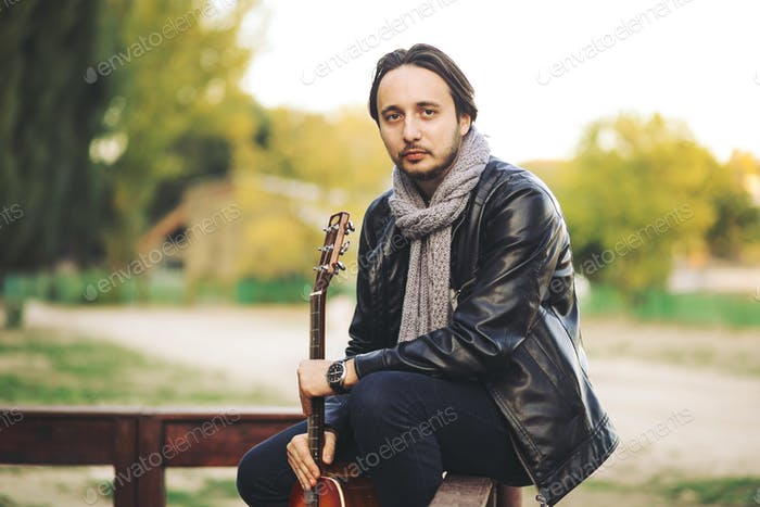 Young man playing on guitar at the lake