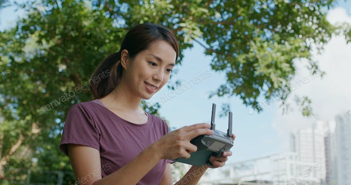 Woman control a fly drone at outdoor