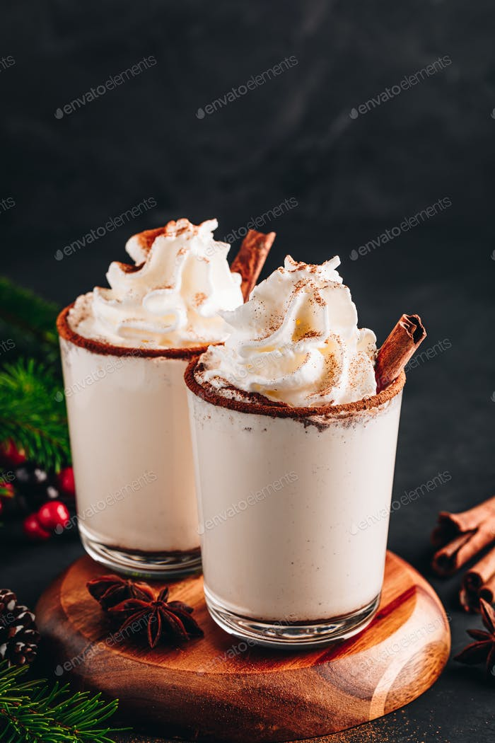Traditional Christmas drink Eggnog with whipped cream and cinnamon on dark stone background.