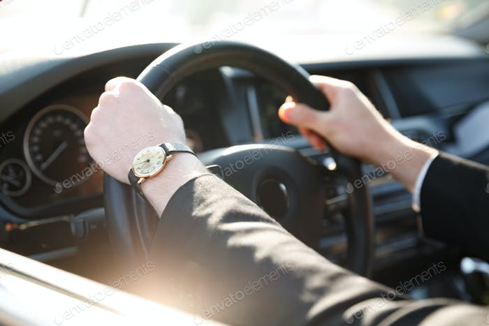Cropped image of business man driving car