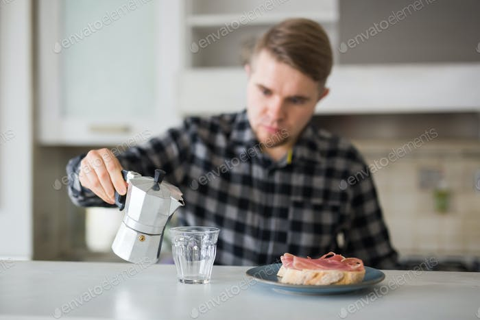 People, breakfast and drinks concept - handsome bearded young man is drinking coffee in kitchen