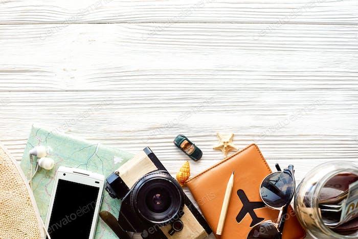 Camera, sunglasses, passport, money, map, phone, hat, car, plane