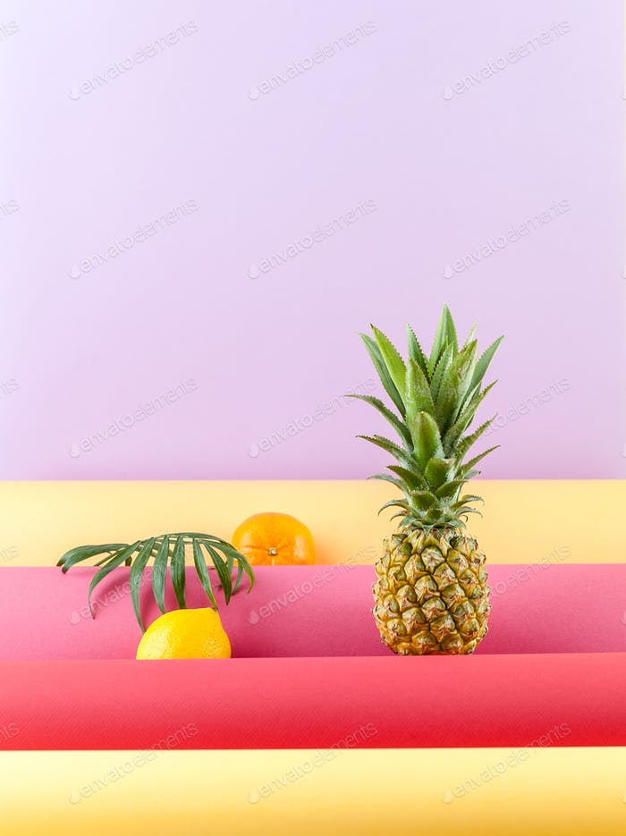 Pineapple, lemon and mandarin on a combined colored background w