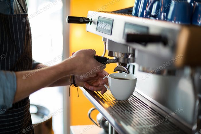 Mid section of waiter making cup of coffee at counter