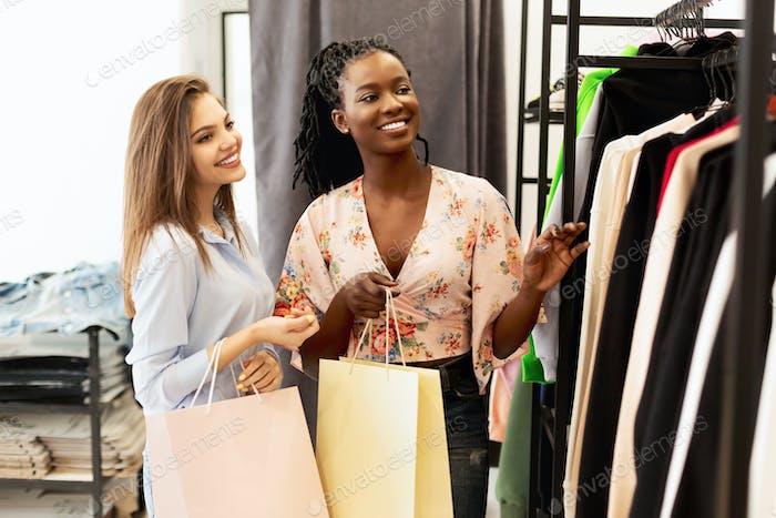 Two Women Shopping In Fashion Store Choosing Seasonal Updates