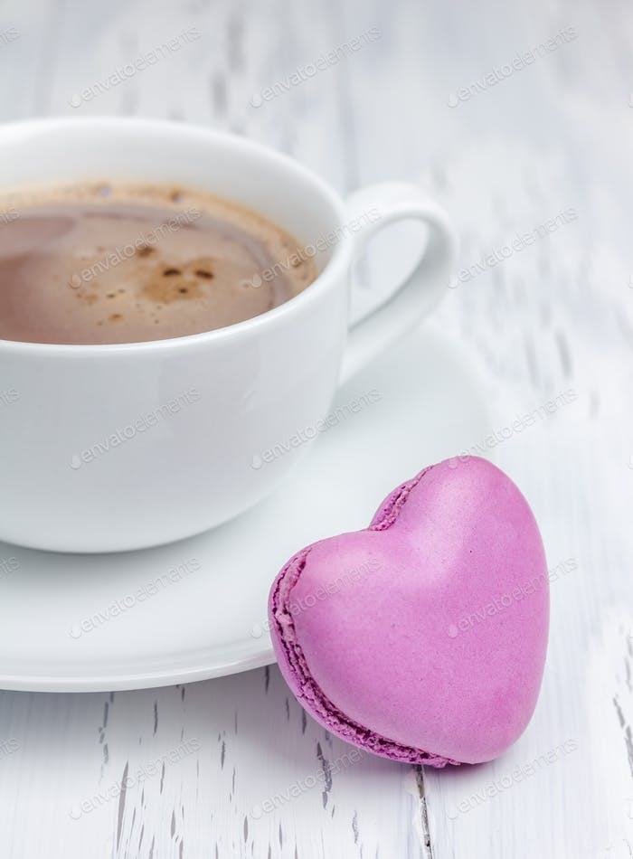 Eine Tasse heiße Schokolade mit einem herzförmigen Macaron (vertikal)