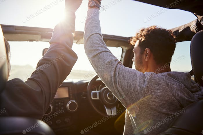 Young couple driving with sunroof open and hands in the air