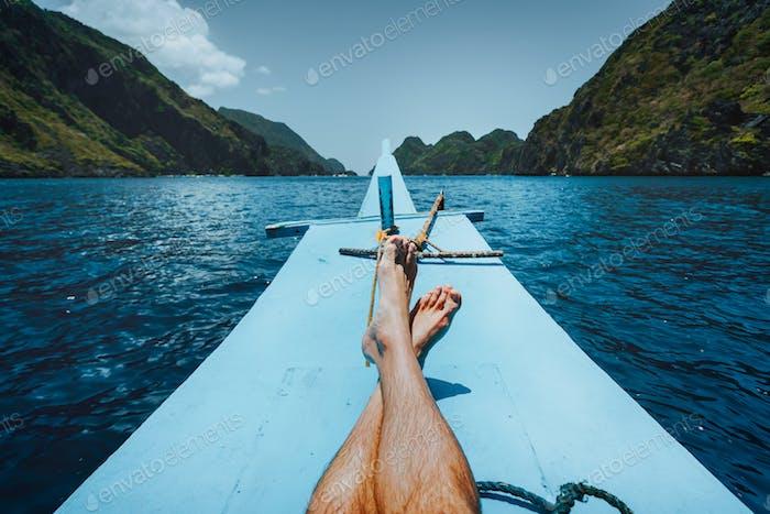 Beine des Menschen auf Banca Boot nähert tropische Insel. Reise, Entspannung und Urlaub Konzept