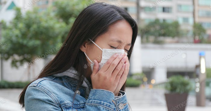 Woman coughing with wearing face mask at outdoor