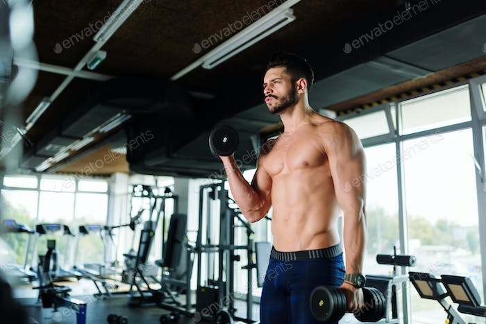 Muscular bodybuilder working out in gym