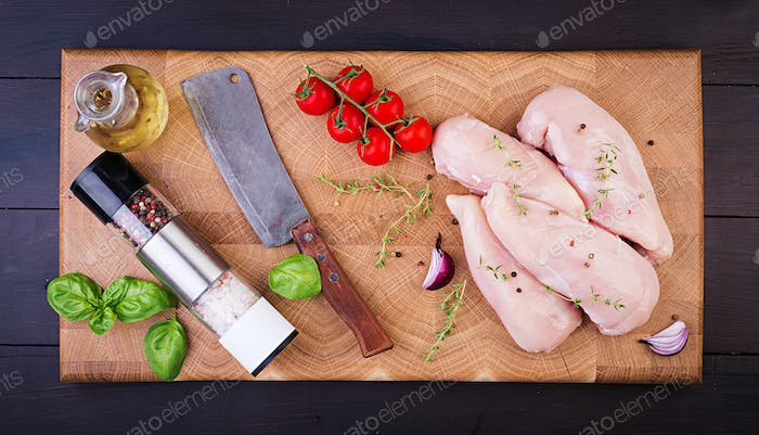 Raw chicken breast fillets on wooden cutting board with herbs and spices. Top view