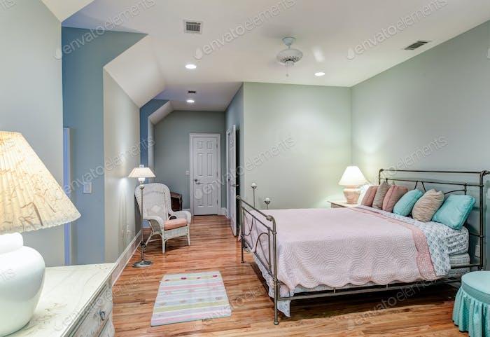 Tasteful attic bedroom with hard wood floors