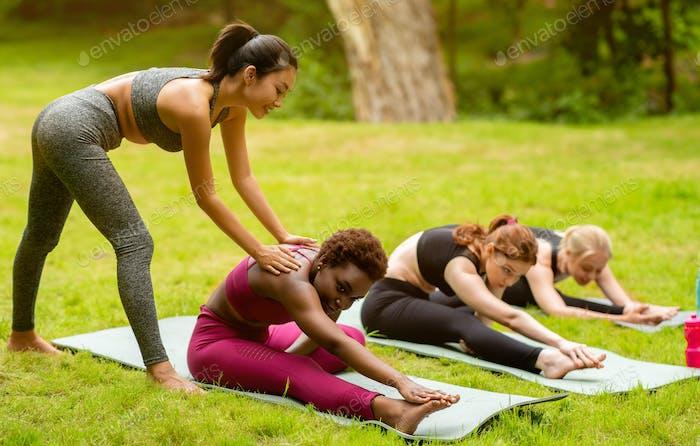Junge weibliche Yoga-Lehrerin Lehrgruppe von sportlichen Frauen zu tun Asanas richtig, außerhalb
