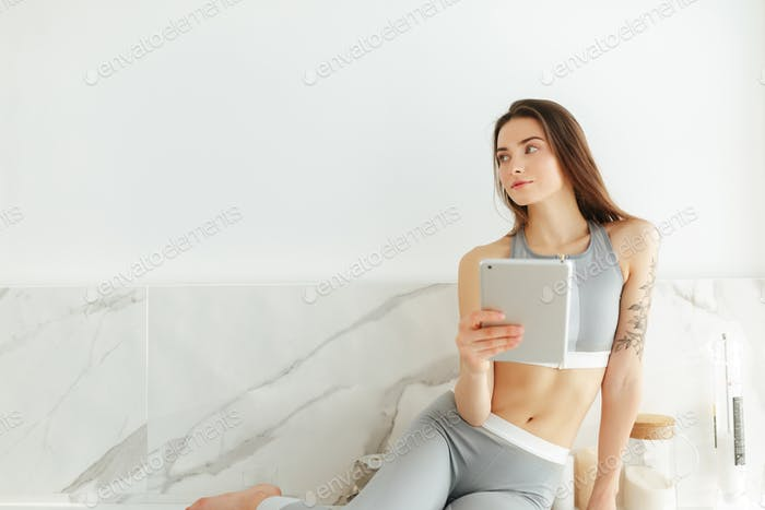 Beautiful lady in sporty top and leggings sitting on kitchen with tablet dreamily looking aside