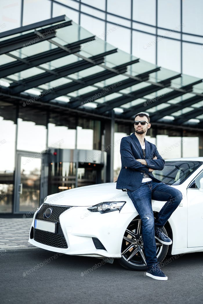 Serious male entrepreneur is standing with his auto in city