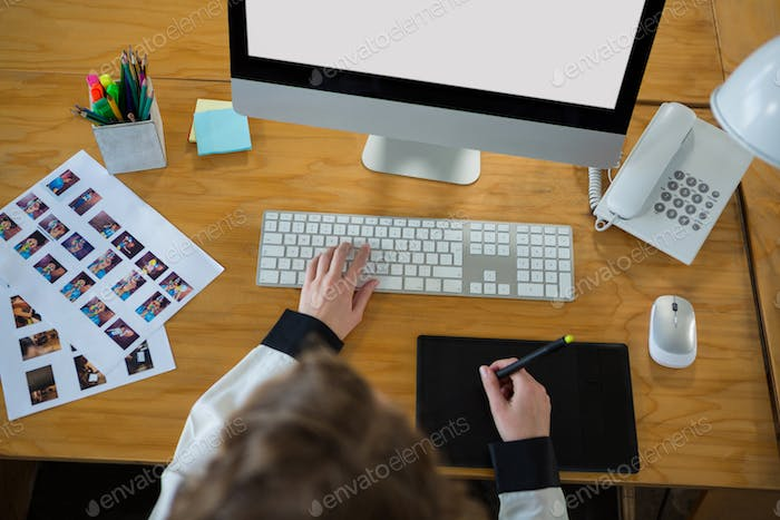 Graphic designer using desktop pc and graphic tablet